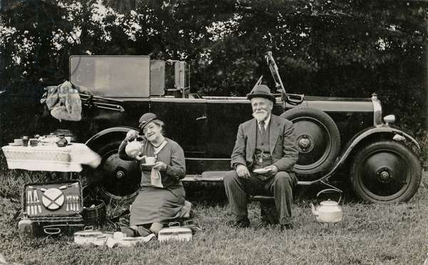 Picnic beside a motor car (b/w photo)