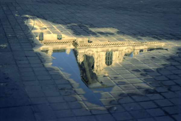 Detail of a pavillon of the Cour Napoleon, Le Louvre reflecting in a puddle (photo)