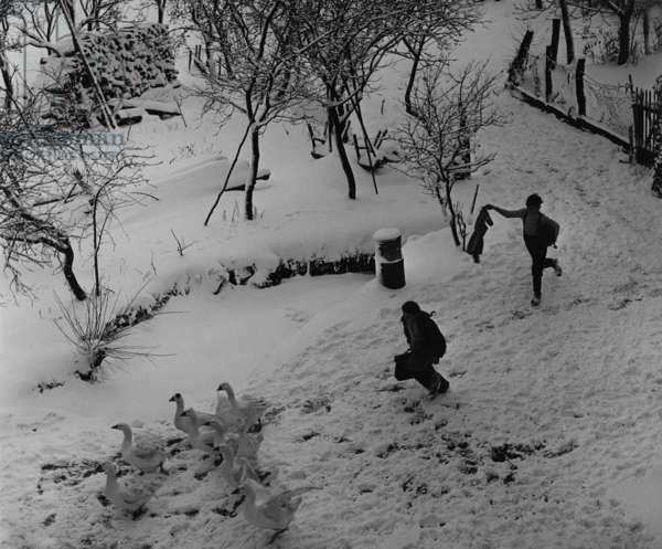 Children running on the way to school in winter (b/w photo)