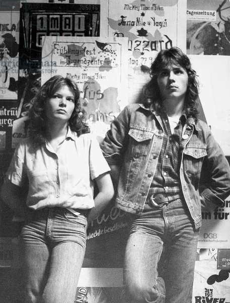 Two teenagers leaning against a wall with concert and event posters, 1981 (b/w photo)