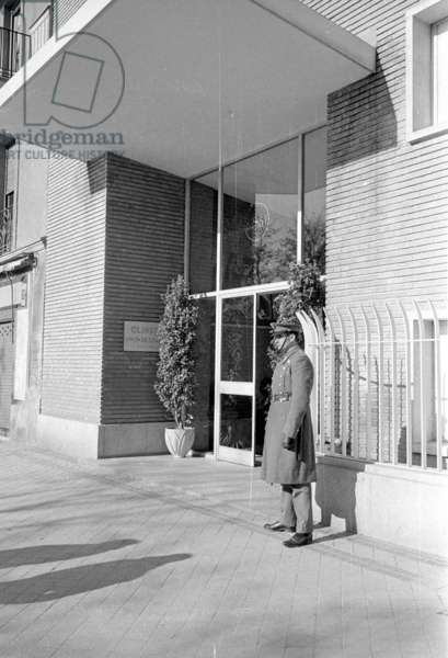 A police officer in front of a hospital in Madrid, 1963 (b/w photo)