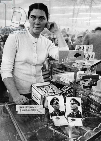 Saleswoman with Erwin Rommel chocolate, 1956 (b/w photo)