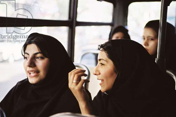 Women chat animatedly on a bus in Tehran 2001 (photo)