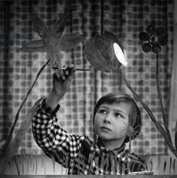 A girl decorating a window, 50s (b/w photo)