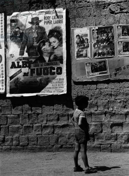 Boy in front of film posters (b/w photo)