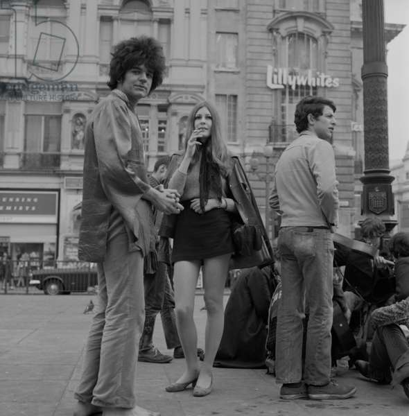 A group of young people smoking and playing music, Piccadilly Circus, London, 1968 (b/w photo)