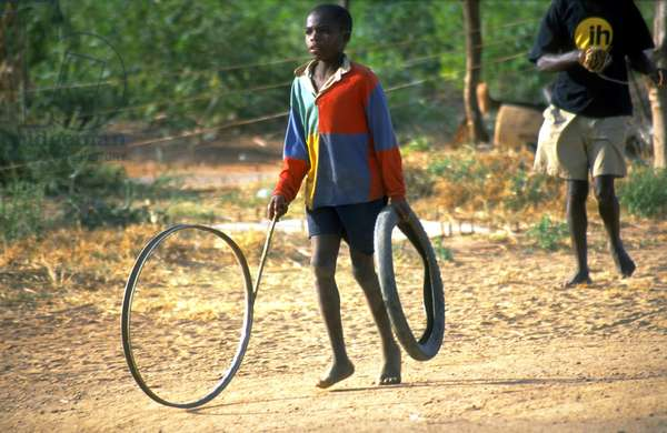 Boy playing with tire, Malawi, 2000 (photo)