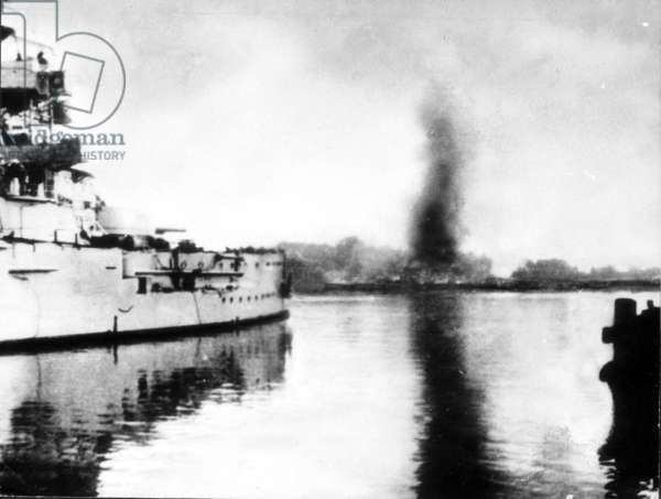 The warship 'Schleswig-Holstein' firing on the Polish fort at Westerplatte, near Danzig, which can be seen burning in the background, 1st September 1939 (b/w photo)
