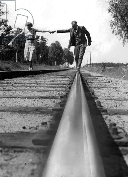 A couple walking along railway tracks, 1934 (b/w photo)