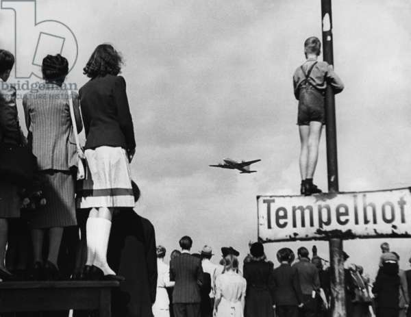 Berliners watching the arrival of the American Rosinenbomber, from the S-Bahn Station, Tempelhof, Berlin, 30th September, 1948 (b/w photo)