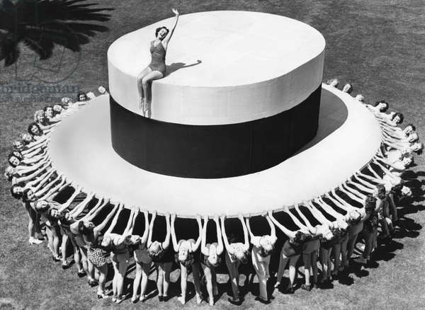 Jane Lawson sitting on a huge hat, surrounded by 50 women for a hat advertisement, Long Beach, California (b/w photo)