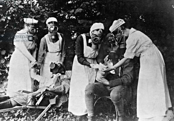 Nurses administering first aid to injured German soldiers following a gas attack, 1917 (b/w photo)