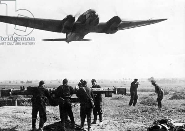 A German plane setting off to attack Poland with soldiers from a flak battery in the foreground, September 1939 (b/w photo)