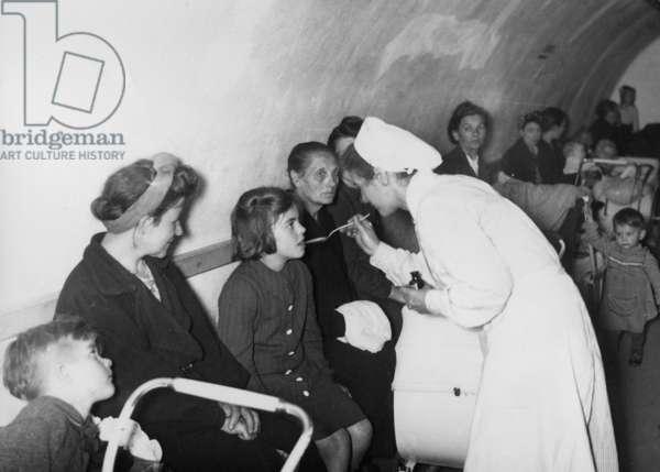 Red Cross nurse in an air-raid shelter, 1943 (b/w photo)
