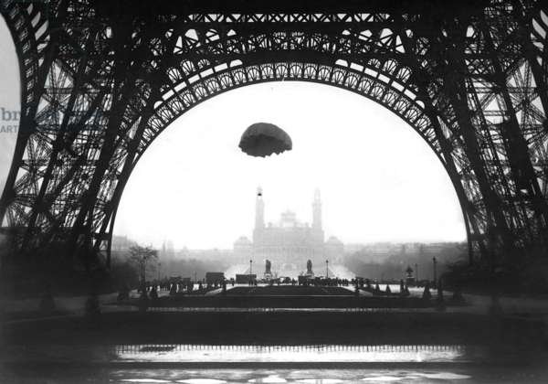 A parachute developed by the inventor Ors descends in front of the Eiffel Tower in Paris, 1913 (b/w photo)