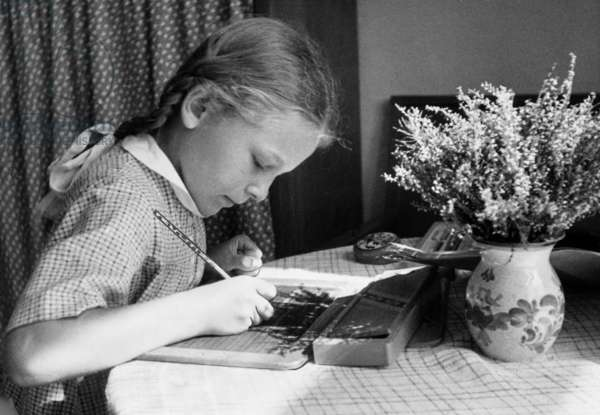 A girl seated at a table does her homework on a slate, 1941 (b/w photo)