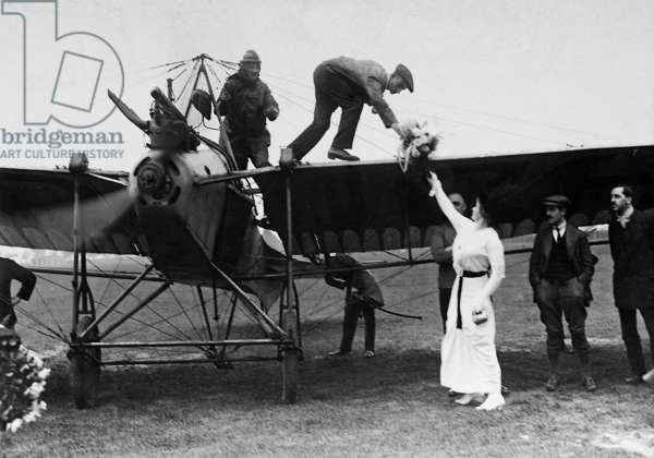 At the Berlin-Johannisthal airfield, the pioneer and owner of the aircraft repair plant in Strausberg Alfred Friedrich is greeted by a woman with flowers after he successfully completed the Berlin-Paris-London-Berlin route. His plane was the so-called Etrich pigeon built by himself. The first long-haul flight Berlin-Paris-London-Berlin over a distance of 2500 kilometres in September 1913, in which the then 22-year-old Alfred Friedrich crossed the canal twice with a passenger on board, represented an enormous achievement in that stage of development of international aviation, 1913 (b/w photo)