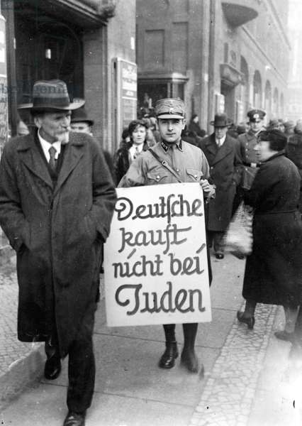 An SA officer carries a sign through Berlin, encouraging citizens to boycott Jewish shops, Berlin, 1st April 1933 (b/w photo)