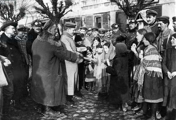 German soldiers hand food to the children in Lodz, 1914 (b/w photo)