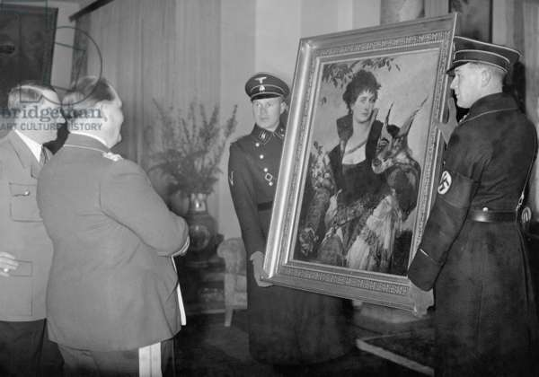 Adolf Hitler presents Hermann Goering with a painting by Hans Makart, 'The Falconer' (1880), held by two men of the SS, Berlin, 1938 (b/w photo)