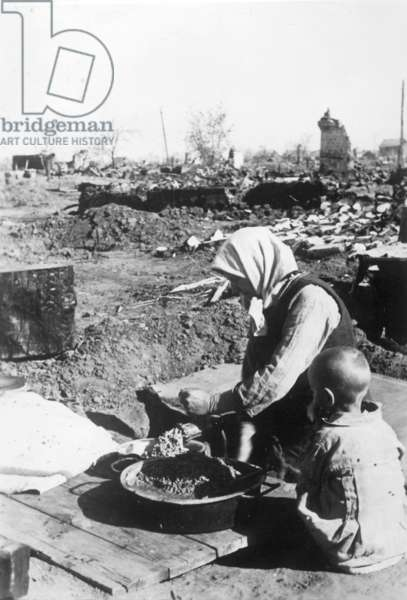 A homeless russian women makes a meal in the ruins of Stalingrad, October 1942 (b/w photo)