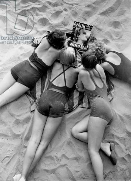 Four women lying in Wannsee beach and reading the magazine 'Berlin', 1935 (b/w photo)
