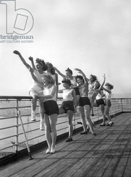 Members of the female auxiliary corps of the Kriegsmarine wave outgoing warships, 1943 (b/w photo)