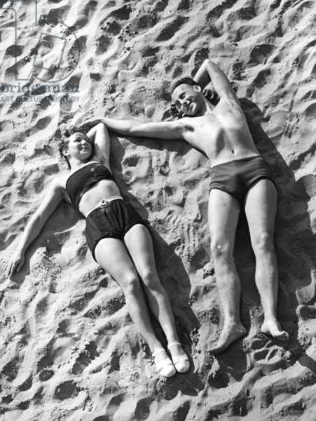 Young couple sunbathing, 1939 (b/w photo)