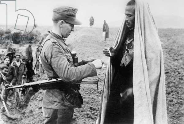A German soldier gives a cigarette to a Tunisian, Tunisia, 1942 (b/w photo)