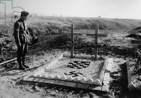 A Croatian volunteer stands at a grave for his comrades who fell in the battle of Stalingrad, December 1942 (b/w photo)
