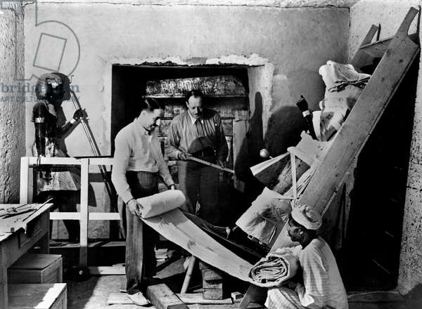 Discovery of the tomb of pharaoh Tutankhamun in the Valley of the Kings (Egypt) : Howard Carter and Arthur Callender in the antechamber at doorway of sepulchral hall, protecting a sentinel statue, november 29, 1923, photo by Harry Burton (p0491)