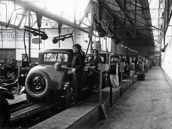 Women working on assembly line, in a Peugeot factory, c. 1929.