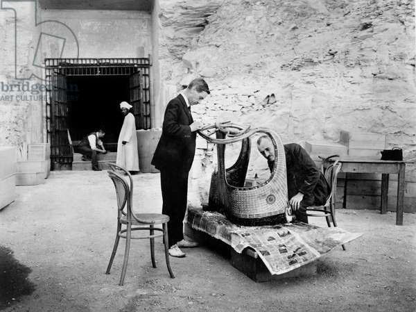 Discovery of the tomb of pharaoh Tutankhamun in the Valley of the Kings (Egypt) : Arthur Mace (g) and Alfred Lucas outside the makeshift laboratory (tomb of Sethos II) with a chariot of the antechamber, december 1923, photo by Harry Burton (p0517)