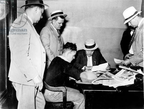 Robert Burns (sweater seated) accused to have kidnapped and killed the son of pilot Charles Lindbergh is questioned on june 11, 1932 (he will be released)