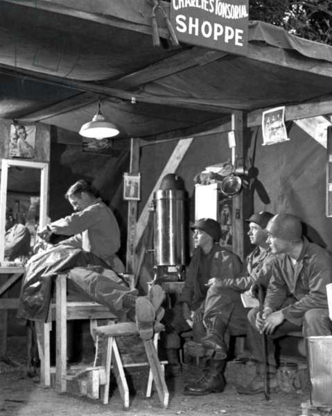 "american soldiers waiting for shaving at ""Charlie's Tonsorial Shoppe"" (named after the corporal Charlie Vaughan, the barber at work) during operations in Normandy june-july 1944 after the allied landings"
