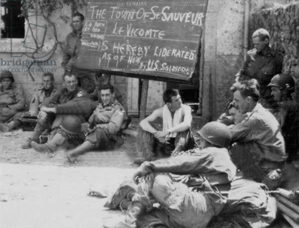 American airborne infantrymen rest in liberated French village of Saint Sauveur in Normandy beside signs which they painted after the hard won battle on Cherbourg peninsula, june 23, 1944