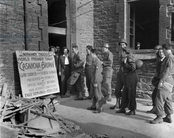American soldiers and red Cross workers stop to read the sign before going in to attend the world premiere of film