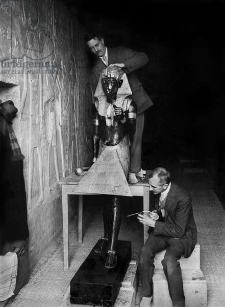 Discovery of the tomb of pharaoh Tutankhamun in the Valley of the Kings (Egypt) : Arthur Mace (standing) and Alfred Lucas in the makeshift laboratory (tombe of Sethos II) with one of the 2 sentinel statues of the antechamber, january 1924, photo by Harry Burton (p0493)