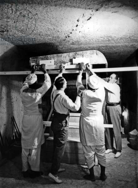 Discovery of the tomb of pharaoh Tutankhamun in the Valley of the Kings (Egypt) : here in burial chamber, Howard Carter, Arthur Callender and egyptian workers removing the lifting one roof section from the first, outermost shrine, december 1923, photo by Harry Burton (p0605)