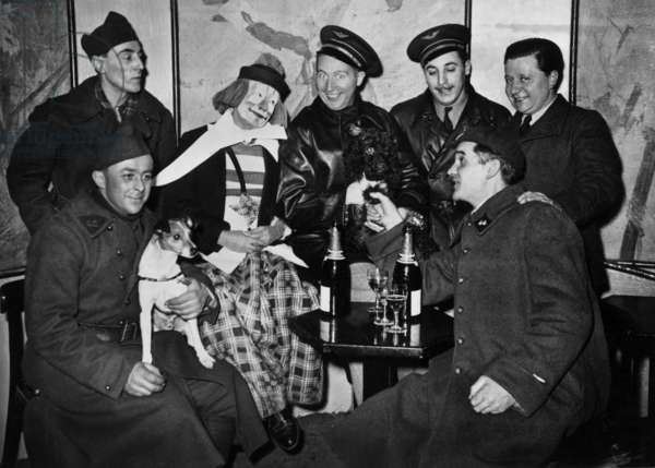 """French singer Charles Trenet (c) with his friend of Medrano circus : on left are the kings of the flying trapeze, then the clown Boulicot, in the centre Charles Trenet, on his left Jerome Medrano and on the foreground """"Monsieur Loyal"""" (presenter of the show), january 1940"""