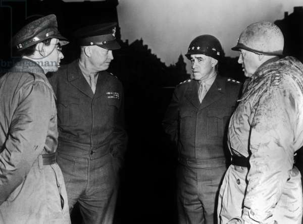 Amid shattered ruins of Bastogne in Belgium, General Eisenhower, Supreme Allied Commander, chats with Lt Gen George Patton of the 3rd Army, and Lt Gen Omar Bradley, C G of the 12th Army group, during a tour of the front, extreme left is Sgt Jules Grad American reporter 1945, Liberation of Belgium Liberation,  Battle of the Bulge