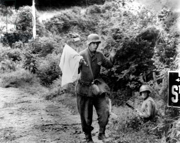 Young german soldier surrenders with white flag to the american troops near the city of Saint Lo, Normandy during the violent fights with the Allies to liberate the city, july 20, 1944