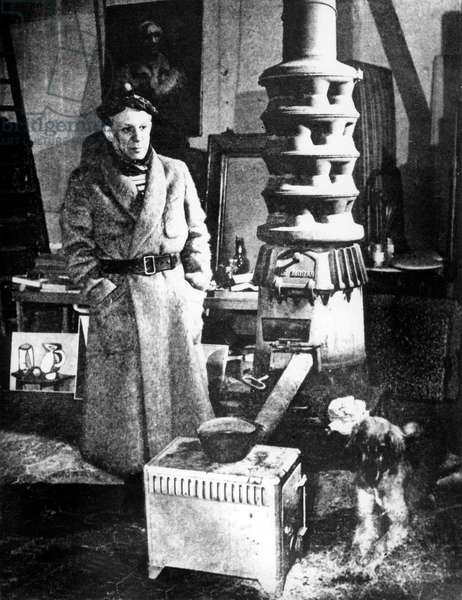 Pablo Picasso (1881-1973) and his afghan hound dog Kazbek in his workshop at 7, rue des Grands-Augustins in Paris c.1939-1944