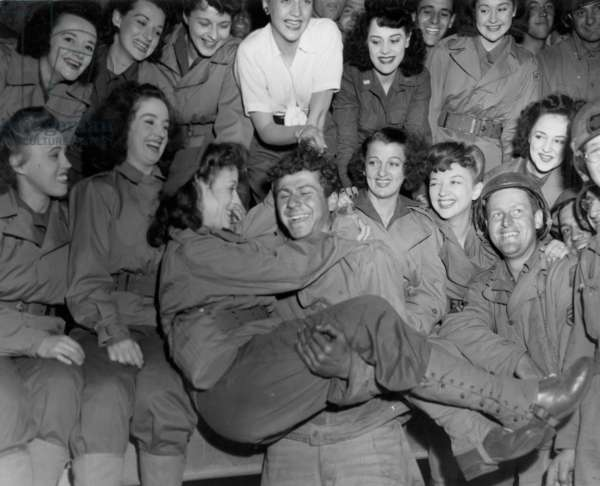 On july 26, 1944, in Normandy in France, an american soldier gets an armful of beauty as a U.S.O camp show puts on their 1st entertainment for american troops on the continent, photo NARA