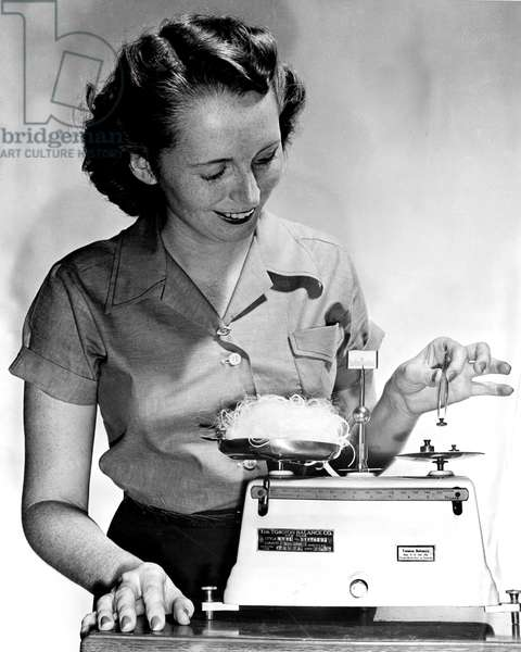 Janet Nessik, employee of the Dupont Company, weighs a half ounce of nylon yarn, enough to make one pair of women's hose