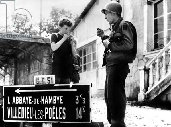 American GI learning a French boy how to chew chewing-gum after the Liberation of Hambye in Normandy, France by the Allied july 29, 1944
