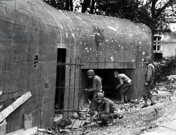 American soldiers taking over the city of Saint Lo : discovering disused blockhouse after the retreat of german troops, july 1944