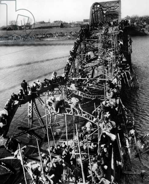 Flight from North Korea which is to communists : refugees clinging to a destroyed bridge in Pyongyang in december 1950, photo NARA