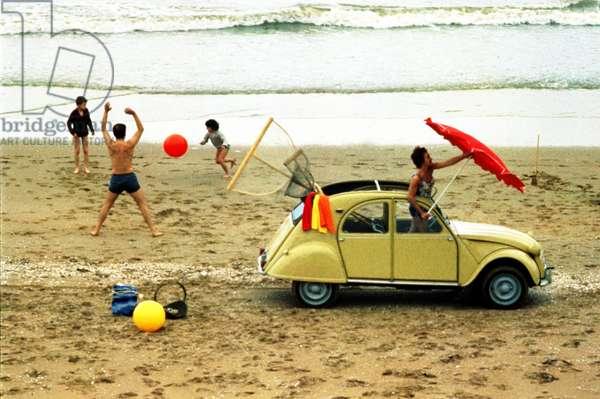 Leisures on beach with a 2 CV convertible car Citroen, c. 1963