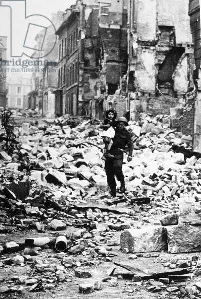 Caen, Normandy, France, july 10, 1944 : among the ruins of the vity destroyed by Allies bombings, an english soldier with a young girl